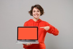 Smiling young brunette woman girl in casual red hoodie isolated on grey background. People lifestyle concept. Mock up copy space. Pointing index finger on laptop pc computer with blank empty screen