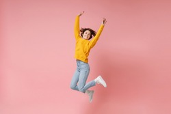 Smiling young brunette woman girl in yellow sweater posing isolated on pastel pink background in studio. People lifestyle concept. Mock up copy space. Having fun fooling around, rising hands, jumping