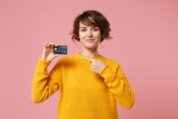 Smiling young brunette woman girl in yellow sweater posing isolated on pastel pink wall background studio portait. People lifestyle concept. Mock up copy space. Point index finger on credit bank card