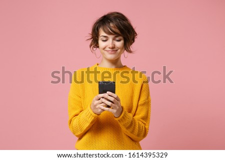 Photo of  Smiling young brunette woman girl in yellow sweater posing isolated on pastel pink wall background studio portait. People lifestyle concept. Mock up copy space. Using mobile phone, typing sms message