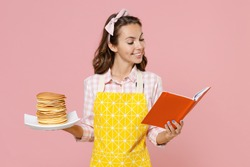 Smiling young brunette woman housewife 20s wearing yellow apron hold plate with pancakes cookery book doing housework isolated on pastel pink colour background studio portrait. Housekeeping concept