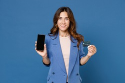 Smiling young brunette woman 20s wearing basic jacket standing hold mobile phone with blank empty screen mock up copy space credit bank card isolated on bright blue colour background, studio portrait
