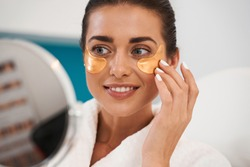 Smiling young brunette woman wearing bathrobe applying cosmetic eye patches while standing at the bathroom mirror