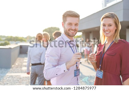 Smiling young business couple looking at the camera whilst they hold a glass of wine and their friends talk in the background