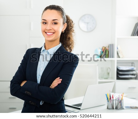 Smiling young business lady with dark hair standing near office desk