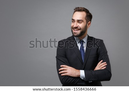 Smiling young business man in classic black suit shirt tie posing isolated on grey background. Achievement career wealth business concept. Mock up copy space. Holding hands crossed, looking aside