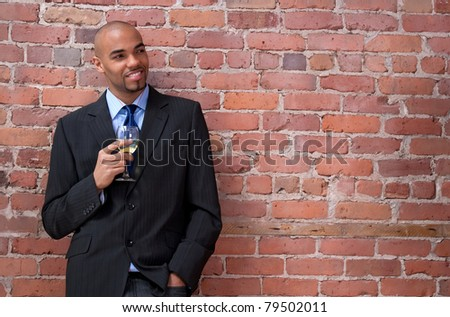 Smiling young business man leaning against the brick wall, smiling and drinking wine. - stock photo