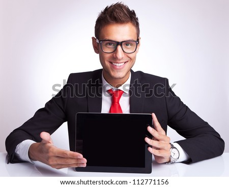 smiling young business man presenting a touchscreen  pad tablet at his desk