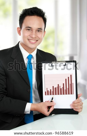 smiling young business man showing growth chart diagram