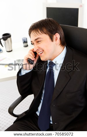 Smiling young business man talking on  telephone in office