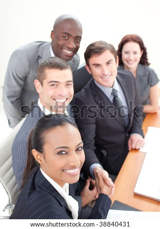 Smiling young business team in a meeting shaking hands