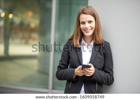 Smiling young business woman using her mobile cell phone