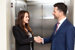 Smiling Young Businessman And Businessman Shaking Hands Near Elevator