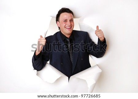 smiling young businessman break through a paper wall
