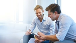 Smiling young businessman discussing something positive with his mature colleague, and using a digital tablet together