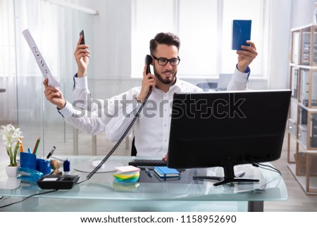 Smiling Young Businessman Doing Multitasking Work At Workplace