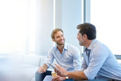 Smiling young businessman enjoying a positive conversation with a mature business partner in a modern space with large windows