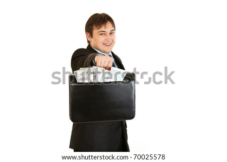 Smiling young businessman giving briefcase with money isolated on white