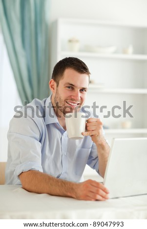 Smiling young businessman having a cup of coffee