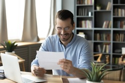 Smiling young businessman in eyeglasses looking at paper correspondence, reading pleasant good news. Excited happy male entrepreneur getting bank loan approvement notification at home office.