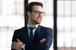 Smiling young businessman in suit and glasses look in window distance thinking or planning career success. Happy Caucasian male director or CEO thinking visualizing in office. Business vision concept.