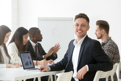 Smiling young businessman in suit looking at camera posing with laptop at group meeting, happy project manager, financial analyst, successful accountant or professional executive employee portrait