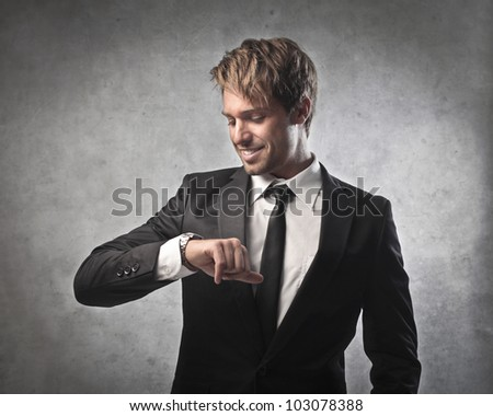 Smiling young businessman looking at his wristwatch