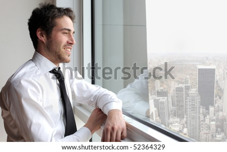 Smiling young businessman looking out of a window