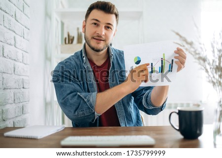 Smiling young businessman sit at desk and talk by webcam with business colleague, shows a graph with the dynamics of economic growth and discusses about further strategy. Distant work