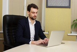 Smiling young businessman sitting behind his desk with laptop in office
