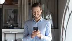 Smiling young businessman standing in modern office, using smartphone applications, setting meeting reminder in mobile organizer or communicating online with clients, people and technology concept.