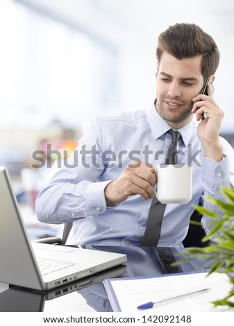Smiling young businessman talking on his mobile phone and drinking coffee in office with laptop computer.