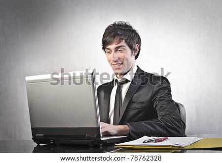 Smiling young businessman using a laptop - stock photo