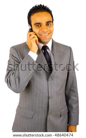 Smiling young businessman using mobile phone against white background