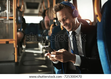 Smiling young businessman wearing a suit sitting on a bus during his morning commute wearing headphones and sending messages on a smartphone
