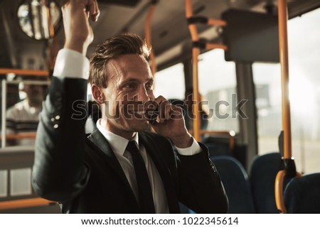 Smiling young businessman wearing a suit standing on a bus during his morning commute talking on a cellphone #1022345614