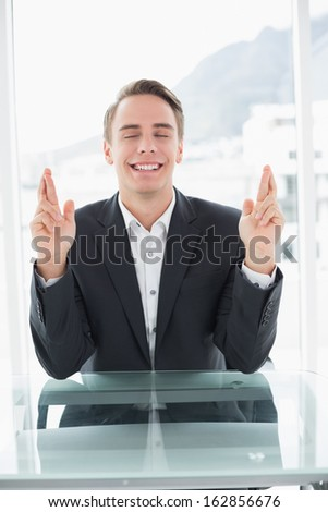 Smiling young businessman with fingers crossed sitting at office desk