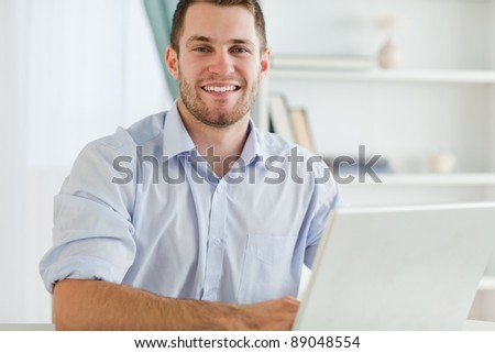Smiling young businessman with rolled up sleeves in his home business #89048554