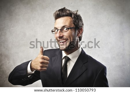 Smiling young businessman with thumbs up