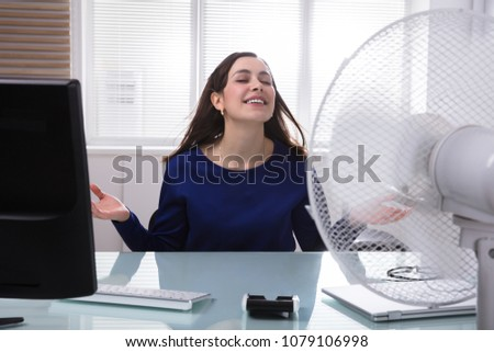 Smiling Young Businesswoman Cooling Herself With Electric Fan During Hot Weather #1079106998