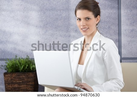 Smiling young businesswoman sitting on sofa with laptop computer in office lobby, looking at camera.?
