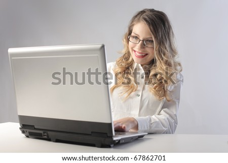Smiling young businesswoman using a laptop - stock photo