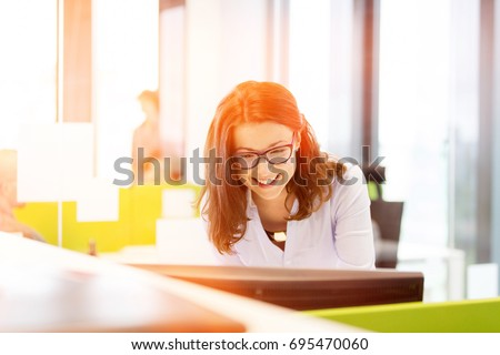 Smiling young businesswoman using computer in office