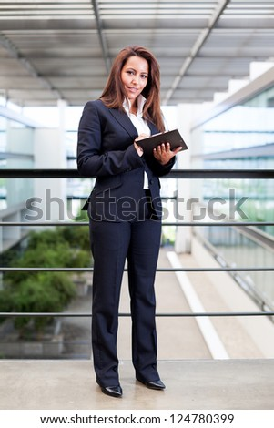 Smiling young businesswoman using his digital tablet at the office