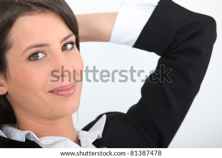 Smiling young businesswoman with her hands behind her head