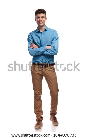 smiling young casual man standing with hands crossed on white backgrouond, full body picture
