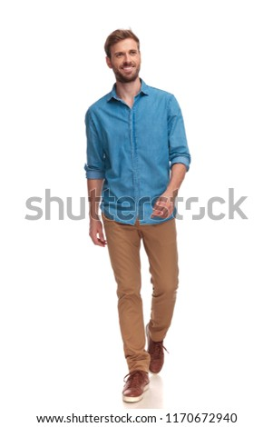 smiling young casual man walking and looking to side on white background #1170672940