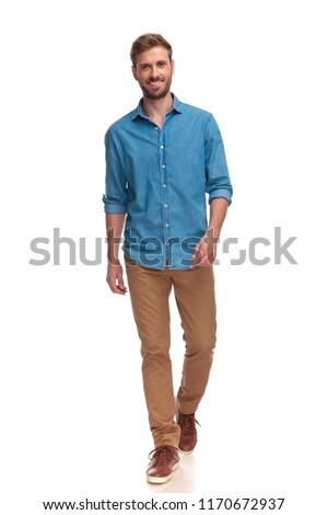 smiling young casual man walking forward on white background #1170672937