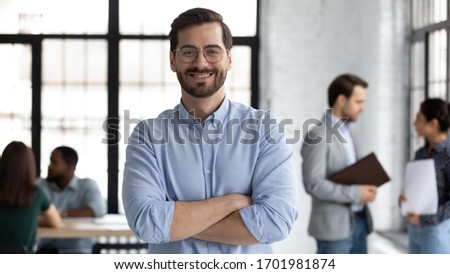 Smiling young Caucasian businessman in glasses stand in modern office show confidence and motivation at work, happy millennial European male CEO posing at workplace, leadership, success concept