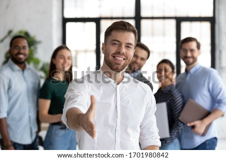 Smiling young Caucasian businessman stretch hand greeting meeting with new office employee or worker, happy male team leader or employer welcome newcomer or intern at workplace, recruitment concept